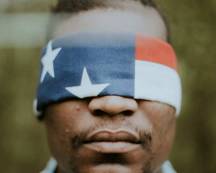 Black man blindfolded with the United States flag