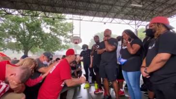White Christians kneel in prayer before Black Christians and apologize while asking for forgiveness for generations of racial injustice against Black communities