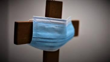 face mask on a cross to convey coronavirus church