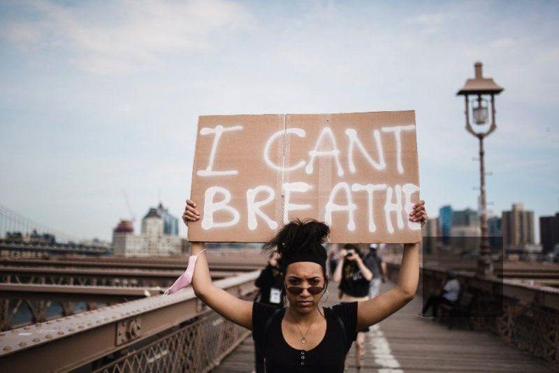 blakc woman holds a i cant breathe sign