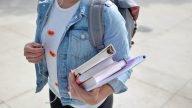 woman wearing blue denim jacket holding book