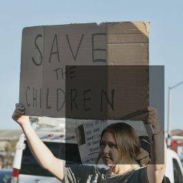 Woman holds Save Children Sign