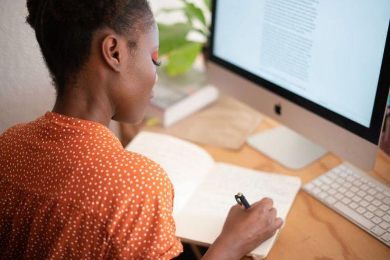 woman takes notes at a computer