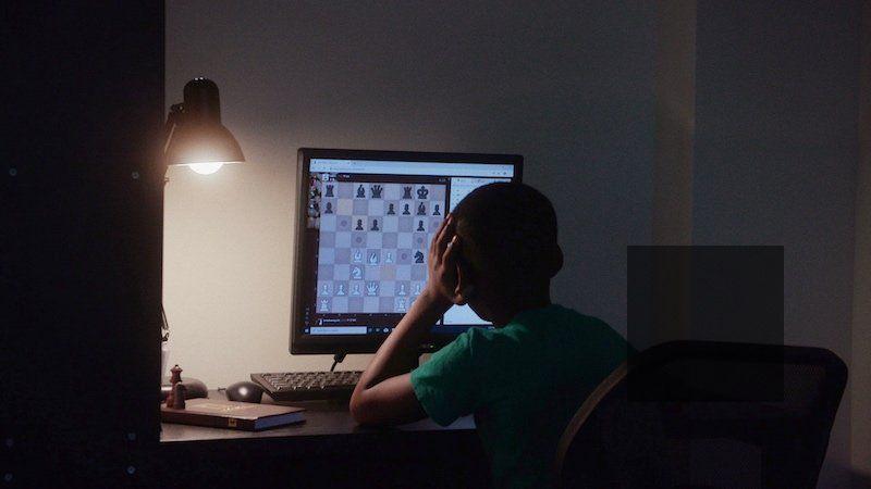 Tani Adewumi works on his chess game on his computer.
